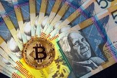 Golden Bitcoin glowing on top of Australian 50 dollar banknotes closeup. stock image