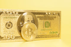 Golden bitcoin with golden U.S. dollar Stock Images