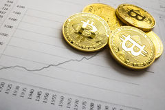 A golden bitcoin on graph background. trading concept of crypto currency Stock Images