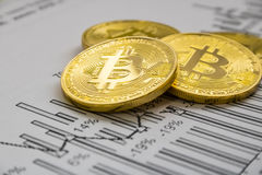 A golden bitcoin on graph background. trading concept of crypto currency Stock Photos