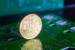 Golden bitcoin on green board with microchips and microcircuits on background. Concept of cryptocurrency, electronic payments and web banking Stock Photo