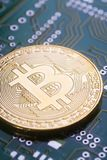 Golden bitcoin on green board with microchips and microcircuits on background. Concept of cryptocurrency, electronic payments and web banking Royalty Free Stock Photo