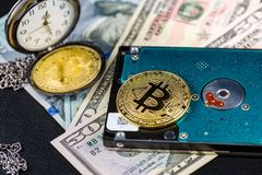 Golden bitcoin on hard disk on us dollars with pocket watch Royalty Free Stock Photo