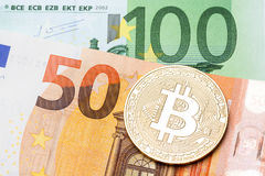 Golden bitcoin on hundred and fifty euro background. High resolution photo Stock Image