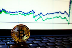 A golden bitcoin with keyboard and graph background. trading concept of crypto currency Stock Images