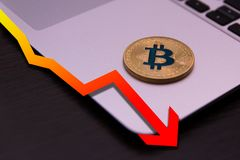 Golden bitcoin lie on silver notebook with falling red graph stock images