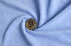 The golden bitcoin lies on a blanket made of soft and fluffy light blue fleece fabric with a large number of relief folds. The sha. Pe of the folds resembles a Stock Photography