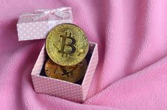 The golden bitcoin lies in a small pink gift box with a small bow on a blanket made of soft and fluffy light pink fleece fabric wi. Th a large number of relief royalty free stock photography