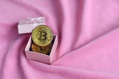 The golden bitcoin lies in a small pink gift box with a small bow on a blanket made of soft and fluffy light pink fleece fabric wi. Th a large number of relief royalty free stock photos