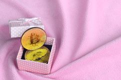 The golden bitcoin lies in a small pink gift box with a small bow on a blanket made of soft and fluffy light pink fleece fabric wi. Th a large number of relief stock photo