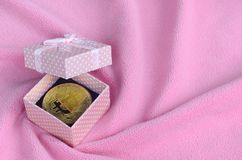 The golden bitcoin lies in a small pink gift box with a small bow on a blanket made of soft and fluffy light pink fleece fabric wi. Th a large number of relief royalty free stock photo