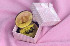 The golden bitcoin lies in a small pink gift box with a small bow on a blanket made of soft and fluffy light pink fleece fabric wi. Th a large number of relief stock image