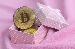 The golden bitcoin lies in a small pink gift box with a small bow on a blanket made of soft and fluffy light pink fleece fabric wi. Th a large number of relief royalty free stock image