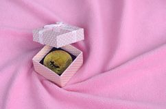 The golden bitcoin lies in a small pink gift box with a small bow on a blanket made of soft and fluffy light pink fleece fabric wi. Th a large number of relief stock photography