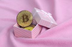 The golden bitcoin lies in a small pink gift box with a small bow on a blanket made of soft and fluffy light pink fleece fabric wi. Th a large number of relief stock photos