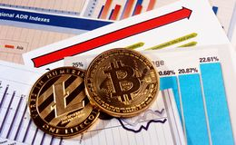 Bitcoin and litecoin on rise graph. A golden bitcoin and litecoin on graph and diagrams background. concept of trading crypto currency Stock Photography
