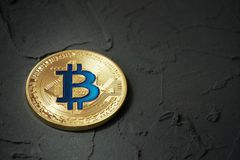 Golden bitcoin lying on a dark, plastered surface stock photos
