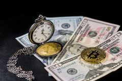 Golden bitcoin lying on us dollars with pocket watch on black Stock Image