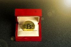 Golden bitcoin in a mahogany box on a black texture background, top view royalty free stock image