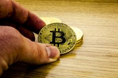 Golden Bitcoin in a man`s hand .Symbol of a new virtual currency . 3D illustration stock photography
