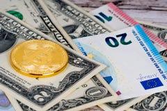 Golden bitcoin metallic coin over dollar and euro stock image