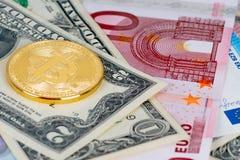 Golden bitcoin metallic coin over dollar and euro stock photo