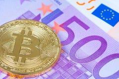 Golden bitcoin metallic coin over euro banknotes close up shot stock photos