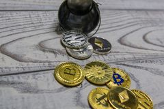 Golden bitcoin and other crypto currency in the fallen toy metal bucket closeup stock photography