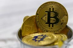 Golden bitcoin and other crypto currency in toy metal bucket closeup. Golden bitcoin and other crypto currency in toy metal bucket royalty free stock photos