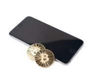 Golden bitcoin over the mobile phone Stock Image