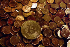 Golden bitcoin over a stack on  coins. Golden bitcoin over a stack on penny coins Royalty Free Stock Photo