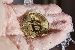 Golden bitcoin in the palm of a hand. Money laundering stock images