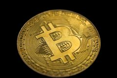 Golden bitcoin physical. Macro shot, isolated on black background Royalty Free Stock Photos