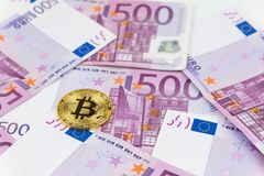 Golden bitcoin on pile of five hundred euro banknotes background royalty free stock image