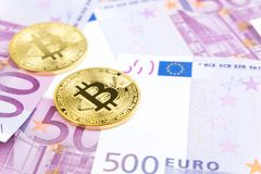 Golden bitcoin on pile of five hundred euro banknotes background stock images