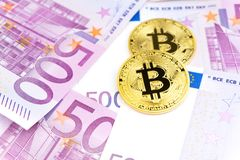 Golden bitcoin on pile of five hundred euro banknotes background royalty free stock photography