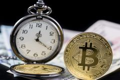 Golden bitcoin and pocket watch near on us dollars Royalty Free Stock Image