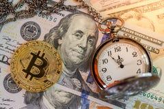 Golden bitcoin and pocket watch on us dollars Stock Photos