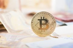 Golden bitcoin on real money background Royalty Free Stock Photos