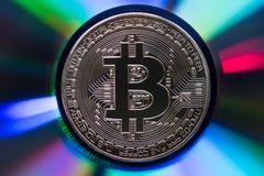 Golden bitcoin on a reflective iridescent multicolor surface Stock Photos