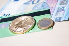 Bitcoin, euros and a credit card. A golden bitcoin, some metal and paper euros and a green credit card Royalty Free Stock Photography