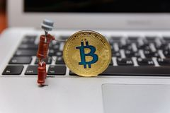 Golden bitcoin stand on silver notebook keyboard stock images