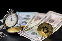 Golden bitcoin standing and retro pocket watch on us dollars. With black background Royalty Free Stock Image