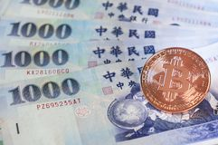 Golden bitcoin on 1000 Taiwanease dollar bills background, with stock photography