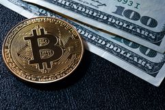 Golden bitcoin on top of dollar banknote background new currency. Accepting stock image