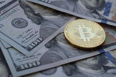 Golden Bitcoin on US dollars. Digital currency close-up. New virtual money. Crypto currency top view. stock photography