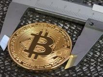 Golden Bitcoin and vernier caliper. Royalty Free Stock Photography