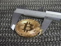 Golden Bitcoin and vernier caliper. Stock Images