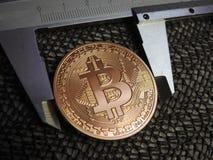Golden Bitcoin and vernier caliper. Stock Photo