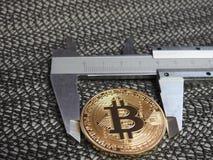 Golden Bitcoin and vernier caliper. Stock Photography